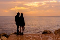 A couple looks at the sea at sunset royalty free stock photography