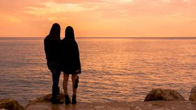 A couple looks at the sea at sunset royalty free stock images
