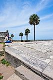 A couple looks sits on an embankment at Castillo De San Marcos while gazing on to Mantazas River. A couple gazes at a view of Mantazes River while sitting on an Royalty Free Stock Images