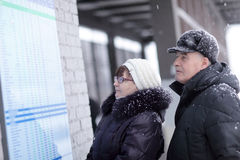 Couple looks at train schedule Stock Images