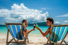 Couple in loungers on a beach at Thailand. Couple in loungers clinking their glasses on a tropical beach at Thailand stock image