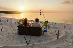 Couple lounging in the Maldives. Couple lounging at sunset on a paradise beach in the Maldives stock images