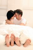 Couple in Love. Smiling couple sitting in bed in love stock image