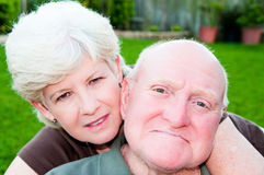 Couple in Love. Closeup portrait of happy, mature couple with wife hugging husband from behind Stock Images