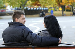 Couple in love. Man hugging a women in autumn park on a bench Royalty Free Stock Images