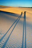 Couple in Love. Two people shadows walking over the sand dune during the sunset royalty free stock images