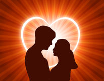 Couple in love. Man and woman in love looking each other at glowing heart background Stock Image
