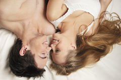 COUPLE IN LOVE. Young couple in love lying in the bed laughing Stock Photography