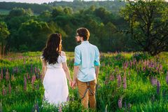 Couple in love admiring beautiful landscape together, holding ha royalty free stock photo