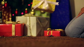 Couple in love arranging a gifts next to christmas tree stock footage