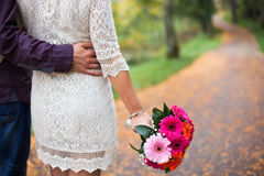 Couple in love on autumn road with pink flowers. Fallen leaves a. Re on way. Bride is dressed in lace white wedding dress royalty free stock image