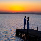 Couple in love back light silhouette at lake. Sunset full length Royalty Free Stock Photography