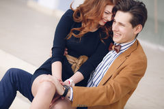 Couple in love on the background of the spring city. Outdoor fashion portrait of happy smiling couple in love having fun together end enjoy their love and Royalty Free Stock Photo