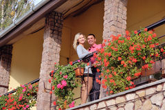 Couple in love on the balcony among the flowers Stock Photography