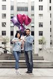Couple in love with the balloons putting hands together. Stock Image