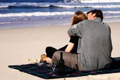 Couple in love on the beach. Couple in love sitting a blanket on the beach enjoying the sea stock photography