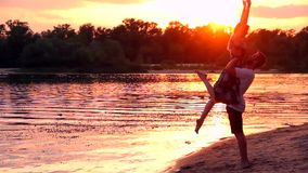 Couple in love on beach. Male / man raising up female / woman on beach near water / river in spring / summer during sunset and kissing. Couple in love concept stock video