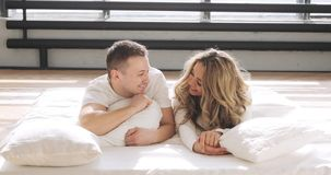 Couple in love in bed are looking at camera and smiling. Man is kissing his girlfriend gently on the forehead. stock video