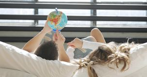 Couple in love in bed are looking at globe choosing a place to travel on honeymoon. stock video