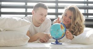 Couple in love in bed are looking at globe spins it and points at random choosing a place to travel on honeymoon. stock video footage