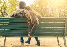 Couple in love on a bench. Couple on a bench - Two lovers sitting on a bench in a park and holding themselves by hands - Concepts of autumn,love,togetherness Stock Images