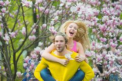 Couple in love in blossoming flower, spring. Man and women in spring, easter. Spring, nature and environment. Sensual women and men in magnolia bloom. Love and royalty free stock image