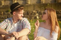 Couple in love blowing blowballs flowers in faces of each other. Smiling and laughing people having good time outside Stock Images
