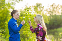 Couple in love blowing blowballs flowers in faces of each other. Smiling and laughing people having good time outside on Royalty Free Stock Photography
