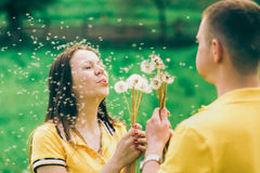 Couple in love blowing cheerfully blowballs flowers Stock Images