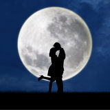 Couple in love on blue full moon silhouette. Silhouette of couple kissing under full moon Royalty Free Stock Photography