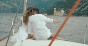 Couple in love on the boat. Look from behind at man and woman hugging each other while they sit on the boat riding