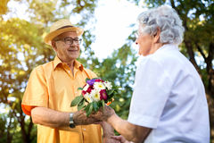 Couple in love with bouquet, senior man giving flowers to his lo Royalty Free Stock Image