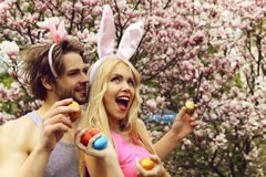 Couple in love with bunny ears holding colorful eggs. On floral environment. Handsome man, macho or boyfriend and cute girl, pretty women or girlfriend smiling stock images