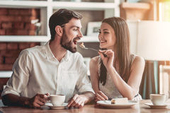Couple in love in cafe. Beautiful couple in love is sitting in cafe, drinking coffee and eating cheesecake. Young women is feeding her man. Looking softly on royalty free stock photos