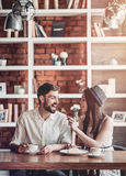 Couple in love in cafe. Beautiful couple in love is sitting in cafe, drinking coffee and eating cheesecake. Young women is feeding her man. Looking softly on Stock Photography
