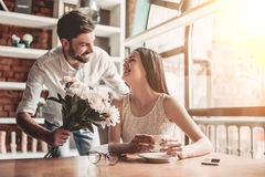 Couple in love in cafe. Surprise! Beautiful romantic couple in cafe. Young men is presenting flowers to his beloved. Feel of happiness Stock Photo