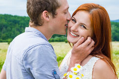 Couple in love on camomile field Stock Photography