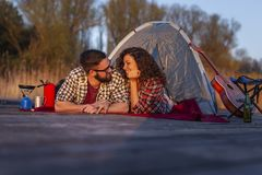 Couple camping. Couple in love camping at the lake docks, lying at the tent entrance and enjoying beautiful sunset stock photo