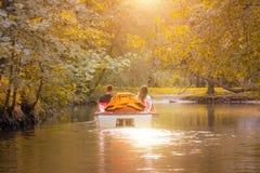 Couple in love in a catamaran, water bike in a park in autumn, sunset. Stock Photos