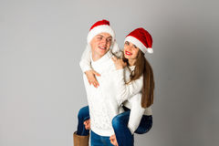 Couple in love celebrates christmas in santa hat Stock Photos