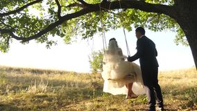 Couple in love celebrates their wedding day. Happy family concept. Bride in white dress and groom swing on swing in park stock video