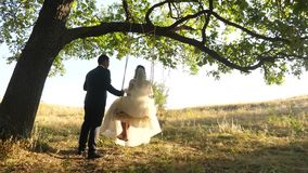 Couple in love celebrates their wedding day. happy family concept. bride in white dress and groom swing on swing in park stock footage