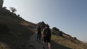 Girl and man go uphill. Couple in love climb a rocky path stock video