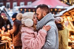 Couple in love, cuddling together and kissing at the winter fair at a Christmas time. An attractive couple in love, cuddling together and kissing at the winter royalty free stock photos