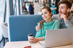 Couple in love on a date in cafe in Valentines day. Man and women drinking coffee and eating desert in a cafe. Two people, men and women with laptop in cafe Stock Photos