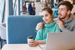 Couple in love on a date in cafe in Valentines day. Man and women drinking coffee and eating desert in a cafe. Two people, men and women with laptop in cafe Stock Photo
