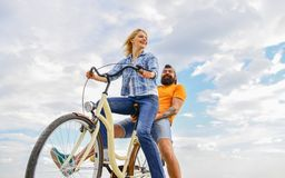 Couple in love date cycling. Couple with bicycle romantic date sky background. Let her be leader. Psychology of. Relationships. Leadership in family and stock photo