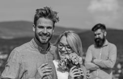 Couple in love dating while jealous bearded man watching wife cheating him with lover. Lovers hugs outdoor flirt romance. Couple in love dating while jealous stock image