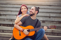 Couple in love dating. Man plays guitar to his girlfriend. Happy couple in love dating. Man plays guitar to his girlfriend royalty free stock images