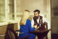 Couple in love dating in restaurant. Woman or girl with blond hair and men or hipster drinking wine from martini glasses. Alcohol and appetizer. Addictive and stock photography